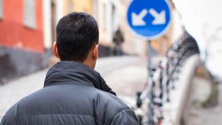 A man walks towards a crossroads.